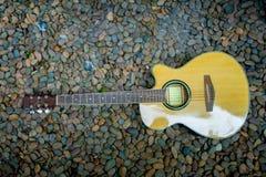 在岩石背景的古典吉他 免版税库存照片