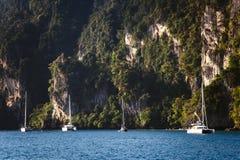 在岩石背景的游艇  免版税库存图片