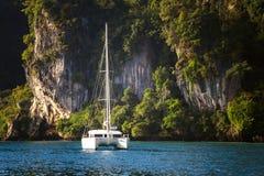 在岩石背景的游艇  免版税库存照片