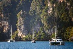 在岩石背景的游艇  免版税图库摄影