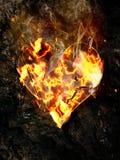 在岩石背景的燃烧的粉碎的心脏 免版税图库摄影