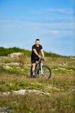 在岩石足迹的有吸引力的运动员骑马自行车反对与云彩的天空 图库摄影