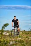在岩石足迹的有吸引力的运动员骑马自行车反对与云彩的天空 免版税库存图片