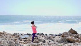 在岩石足迹的白种人有吸引力的妇女奔跑 击中反对海滩的海波浪 桃红色成套装备 t 影视素材