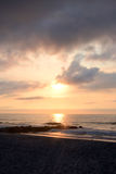 在岩石跳船的天堂般的夏天日出在海滩 免版税库存图片