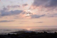 在岩石跳船的天堂般的夏天日出在海滩 库存图片