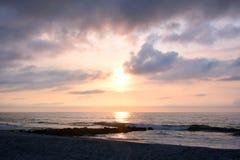 在岩石跳船的天堂般的夏天日出在海滩 免版税库存照片