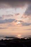在岩石跳船的天堂般的夏天日出在海滩 图库摄影