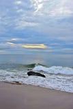 在岩石跳船的平静的夏天日出在海滩 库存图片