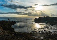 在岩石边缘的人们在海附近 免版税库存图片