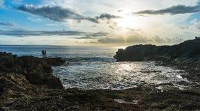 在岩石边缘的人们在海附近 免版税图库摄影
