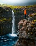 在岩石边缘的年轻男性身分与在背景中使自然风景惊奇 免版税库存照片