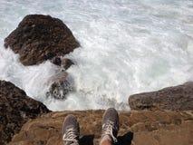 在岩石边缘的脚在有发泡的波浪的海洋 免版税库存照片