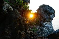在岩石里面的太阳由海 图库摄影