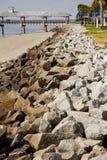 在岩石防波堤之外的木码头 库存图片