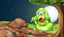 在岩石附近的一个可怕绿色妖怪在树下 库存图片
