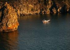 在岩石附近的小船在湖的日落 免版税库存图片