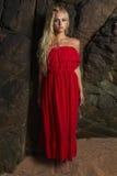 在岩石附近的秀丽时兴的白肤金发的妇女 免版税图库摄影