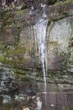 在岩石面孔的冰柱 免版税库存图片
