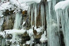 在岩石面孔的冰柱 免版税库存照片