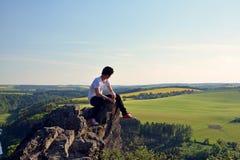 在岩石顶部的年轻人 免版税库存图片