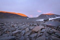 在岩石领域围拢的冰川的惊人的红色焕发日落 免版税图库摄影