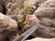 在岩石,旅游梯子的铁舷梯 在块固定的铁扭转的绳索 登山人方式通过ferrata 免版税库存图片