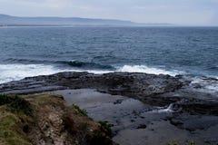 在岩石滚动的岸上和打破波浪 图库摄影