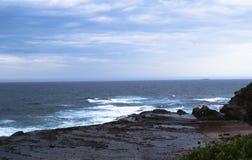 在岩石滚动的岸上和打破波浪 库存照片