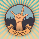 在岩石n卷标志的手 减速火箭的岩石海报 免版税库存照片
