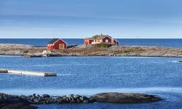 在岩质岛上的挪威红色木房子 图库摄影