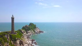 在岩质岛上的灯塔蓝色海空中风景的 峭壁的寄生虫视图灯塔在大海和天空的海洋 股票视频