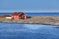 在岩质岛上的红色木房子 挪威 免版税图库摄影