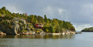 在岩质岛上的红色议院 免版税库存图片