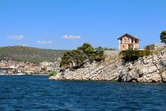 在岩质岛上的议院在对城市希贝尼克,克罗地亚的海途中 图库摄影