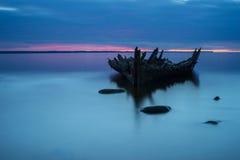 在岸、冻海和美好的蓝色日落背景的老打破的小船击毁 库存照片