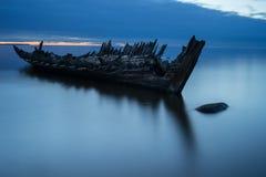 在岸、冻海和美好的蓝色日落背景的老打破的小船击毁 库存图片
