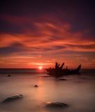 在岸、冻海和美好的蓝色日落背景的老打破的小船击毁 免版税库存图片