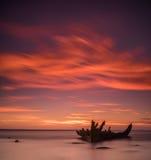 在岸、冻海和美好的蓝色日落背景的老打破的小船击毁 图库摄影