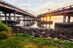 在岸和日出的一座具体槟榔岛桥梁下 免版税库存图片