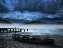 在岸湖的老小船与有薄雾的湖和山大局的 库存图片