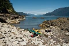 在岸的两艘皮船与山在背景中 免版税图库摄影