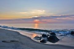 在岸的夏天日出在岩石跳船 库存图片