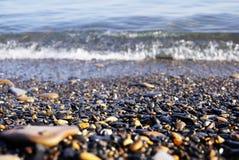 在岸的小卵石在焦点和在背景中海浪和波浪 俄国 免版税库存照片