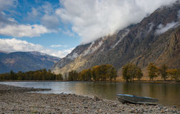 在岸的小船 秋天与河谷、美丽的多云天空和铝小船的山风景在石岸 免版税库存照片