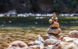 在岸的平衡的石pyramide在自然小河弄脏了背景bokeh 免版税图库摄影
