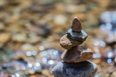 在岸的平衡的石pyramide在自然小河弄脏了背景bokeh 免版税库存照片