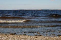 在岸的波浪在一个离开的海滩 河或海海湾,天际 库存照片