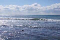 在岸的波浪 在天际附近的云彩 库存照片