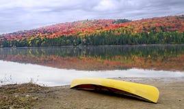 在岸的独木舟与秋天颜色 免版税库存图片